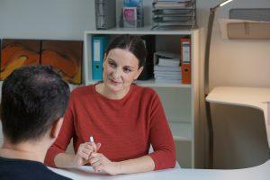 Das ist Sabine Schweighofer im Beratungsgespräch mit einem Klienten.