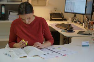 Das ist Sabine Schweighofer bei der Arbeit mit einem Gesetzeskodex und Fachliteratur.
