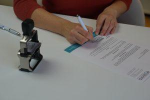 Das ist Sabine Schweighofer bei der Unterschrift eines Briefes.